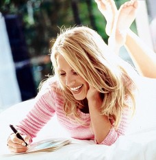 10 Apr 2001 --- Happy woman writing --- Image by © Thomas Schweizer/CORBIS
